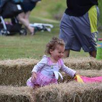 child having fun on bales of hay